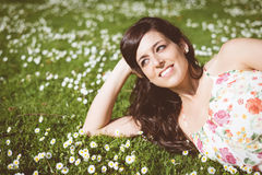 Brunette happy woman relaxing lying on grass Royalty Free Stock Photos