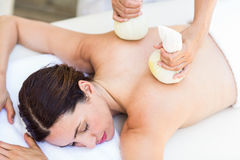 Brunette having massage with herbal compresses Royalty Free Stock Photo