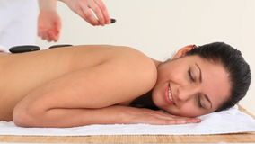 Brunette having a treatment with hot stones Royalty Free Stock Image