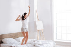 Brunette in headphones jumping on bed Royalty Free Stock Photo