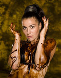 Brunette with her body covered of sweet cream chocolate Royalty Free Stock Photos