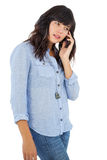 Brunette with her mobile phone calling someone Royalty Free Stock Image