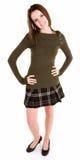 Brunette hermoso en una falda y un suéter de tela escocesa Fotos de archivo libres de regalías