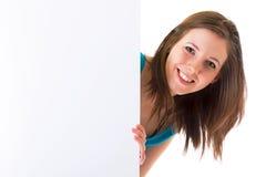 Brunette hermoso que lleva a cabo a la tarjeta blanca vacía Foto de archivo