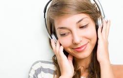 Brunette hermoso sumergido en la música, sonriendo. Foto de archivo