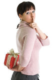 Brunette with hidden Christmas present. Young brunette with hidden red Christmas present isolated over white Stock Image