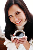 Brunette holding coffee cup Royalty Free Stock Image