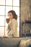 Brunette holding cup of coffee in loft Stock Photo