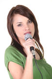Brunette holding microphone Royalty Free Stock Photos