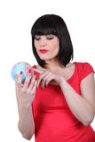 Brunette holding a miniature globe Royalty Free Stock Photos