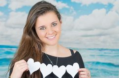 Brunette holding an origami heartshaped paper Royalty Free Stock Photography