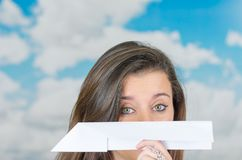 Brunette holding a paperplane in front of cloud Stock Photo