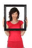 Brunette holding picture frame Stock Photos