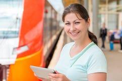 Brunette holding a tablet computer Stock Images