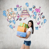 A brunette is holding three gift boxes. Royalty Free Stock Images