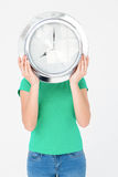 Brunette holding wall clock and hiding her face Stock Photo