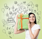 A brunette holds a green gift box. Royalty Free Stock Images