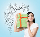 A brunette holds a green gift box. Stock Photography