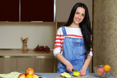 Brunette housewife in blue overalls cuts an apple in the kitchen Stock Images