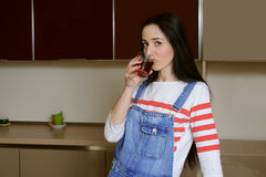 Brunette housewife in blue overalls drinks juice from a glass be Royalty Free Stock Image