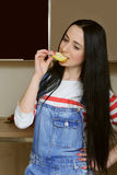 Brunette housewife in blue overalls eating a slice of apple. Stock Photo