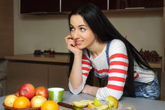 Brunette housewife in blue overalls enthusiastically listens lea Royalty Free Stock Images