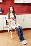 Brunette housewife sitting in kitchen Stock Images