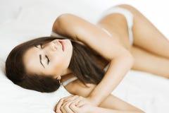 Brunette im Bett Stockfotografie