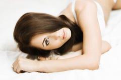 Brunette im Bett Stockfotos