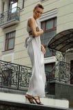 Brunette im langen Kleid nahe einem Hotel Lizenzfreies Stockfoto