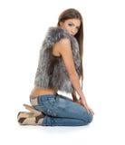 Brunette im Pelz, der auf weißem Hintergrund sitzt Lizenzfreies Stockfoto