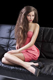 Brunette im Rosa auf Sofa Stockfoto