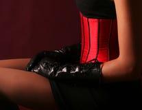 Brunette im roten Korsett über schwarzem Hintergrund stockbild