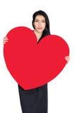 Brunette im schwarzen Kleid mit dem Herzen gemacht vom Papier Lizenzfreie Stockfotografie