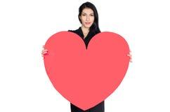 Brunette im schwarzen Kleid mit dem Herzen gemacht vom Papier Stockfotografie