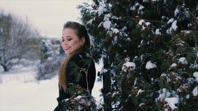 Brunette im Schwarzen steht nahe grünem Busch in der Winterzeitlupe stock video footage