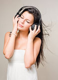 Brunette immersed in music wearing headphones. Royalty Free Stock Photography