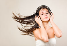 Brunette immersed in music wearing headphones. Royalty Free Stock Images