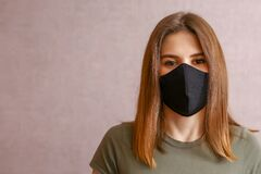 Free Brunette In A Black Mask. A Young Woman In A Cloth Mask On A Light Background. Protection Against Coronavirus Infection, Covid-19 Royalty Free Stock Photo - 187793945