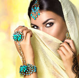 Brunette Indian woman portrait. Indian girl in sari with mehndi. Tatoo and make-up hiding her face behind a veil, smiling and looking in camera. Hindu model Royalty Free Stock Images
