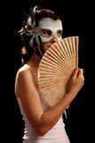Brunette joven con la máscara veneciana y ventilador español Fotografía de archivo