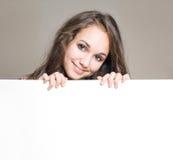 Brunette joven con la tarjeta en blanco. Foto de archivo libre de regalías
