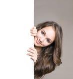 Brunette joven con la tarjeta en blanco. Imágenes de archivo libres de regalías