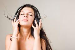 Brunette joven de Gorgoeus sumergido en música. Imagen de archivo libre de regalías