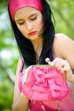 Brunette joven hermoso con el monedero rosado Foto de archivo libre de regalías