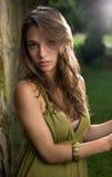 Brunette joven hermoso que presenta en alineada verde. Fotografía de archivo libre de regalías