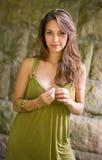 Brunette joven hermoso que presenta en alineada verde. Fotografía de archivo