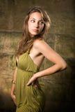 Brunette joven hermoso que presenta en alineada verde. Imagenes de archivo