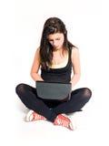 Brunette joven hermoso que trabaja con la computadora portátil. Imagenes de archivo