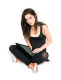 Brunette joven hermoso que trabaja con la computadora portátil. Imágenes de archivo libres de regalías
